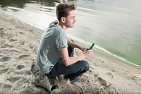 Germany, Berlin, Young man sitting on rock near lake, portrait