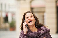 Germany, Bavaria, Munich, Woman using mobile phone, laughing, portrait