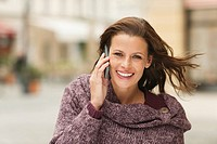 Germany, Bavaria, Munich, Woman using mobile phone, smiling, portrait, close_up