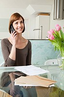 Woman on telephone with bills