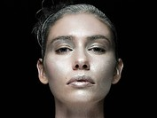 Young woman with face covered in silver make up