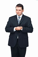 A portrait of young businessman standing with his hands folded together on white background
