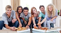 Six friends eating pizza in the living_room on the sofa