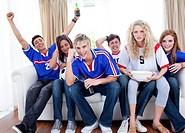 Group of excited and happy teenagers watching a football match at home