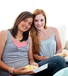 Young girls eating burgers and fries on the sofa
