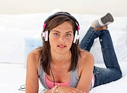 Beautiful teenager sitting on his bed and listening to the music