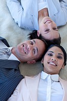 Multi_ethnic business team on floor with heads together smiling