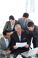 Senior manager showing sales report to his colleagues in a meeting