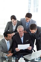 Businessman showing a contract to his team in a meeting