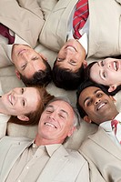 Multi_ethnic business team lying in a circle with heads together
