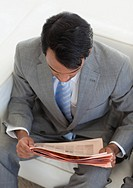 Ethnic businessman reading a newspaper while waiting for a job interview in an office