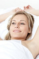 Charming woman relaxing lying on a bed against a white background