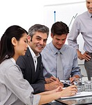 Smiling mature manager in a meeting with his team in the office
