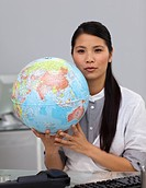 Charming asian businesswoman holding a globe in the office