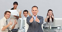 Assertive manager and his team with thumbs up in the office