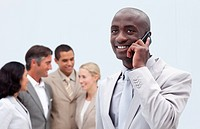 Afro_American businessman talking on mobile phone with his team in the background