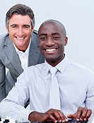 Smiling mature businessman helping his colleague in the office