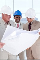 Three engineer co_workers studying plans in a building