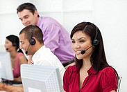 Smiling Customer service representative with headset on in a call center