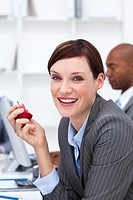 Portrait of a smiling businesswoman eating an apple in the office