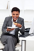 Happy businesswoman eating in the office Business concept