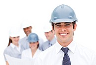 Focus on a male architect wearing a hardhat in front of his team
