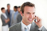 Assertive businessman on phone against a white background