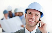 Focus on a male arhitect with a hardhat on phone in front of his team