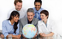 Smiling business people looking at a terrestrial globe in the office