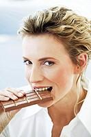 young woman eating big bar of chocolate