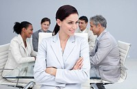 Beautiful businesswoman smiling in a meeting with her colleagues working in the background
