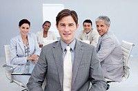 Attractive businessman smiling in a meeting with his colleagues working in the background
