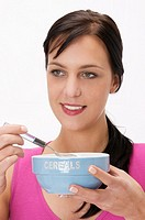 young woman holding a bowl of cereals and having breakfast