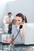 Smiling businesswoman on phone at her desk in the office