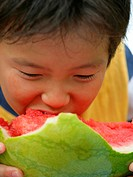 Close_up of a boy eating a slice of a watermelon