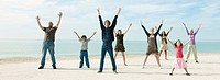 Group of people on beach with arms raised enjoying fresh sea air
