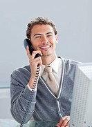 Smiling businessman on phone at his desk in the office