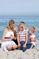 Attentive mother holding sunscreen at the beach with her family