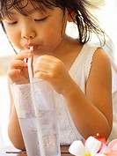 Close_up of a girl drinking water with a drinking straw