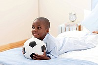 Happy little boy holding a soccer ball lying on his bed