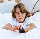 Smiling little boy watching TV lying on the bed
