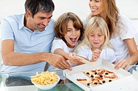 Excited children eating a pizza with their parents in the living_room