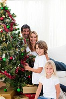 Happy family decorating a Christmas tree with baubles at home