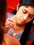Close_up of a young woman applying henna tattoo on another woman's arm