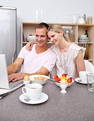 Enamored couple using a laptop while having breakfast in the kitchen