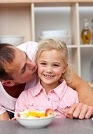 Caring father eating fruit with his daughter in the kitchen