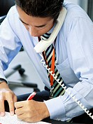 Close_up of a businessman talking on a telephone and writing