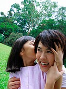 Close_up of a girl whispering into her mother's ear