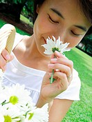 Close_up of a young woman smelling a cosmos flower