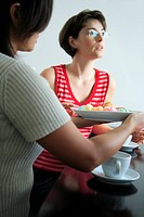 Side profile of a mid adult woman holding a plate of Chinese cakes with her friend sitting beside her at a table